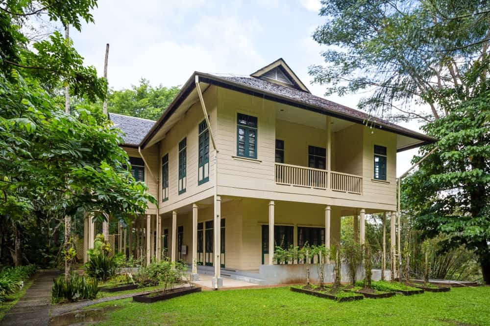 This is a charming wooden home given a Tropical-style landscape to complement its beige exterior walls. There are various tropical trees and shrubberies with some taller than the house and some accenting the concrete walkways on the side.