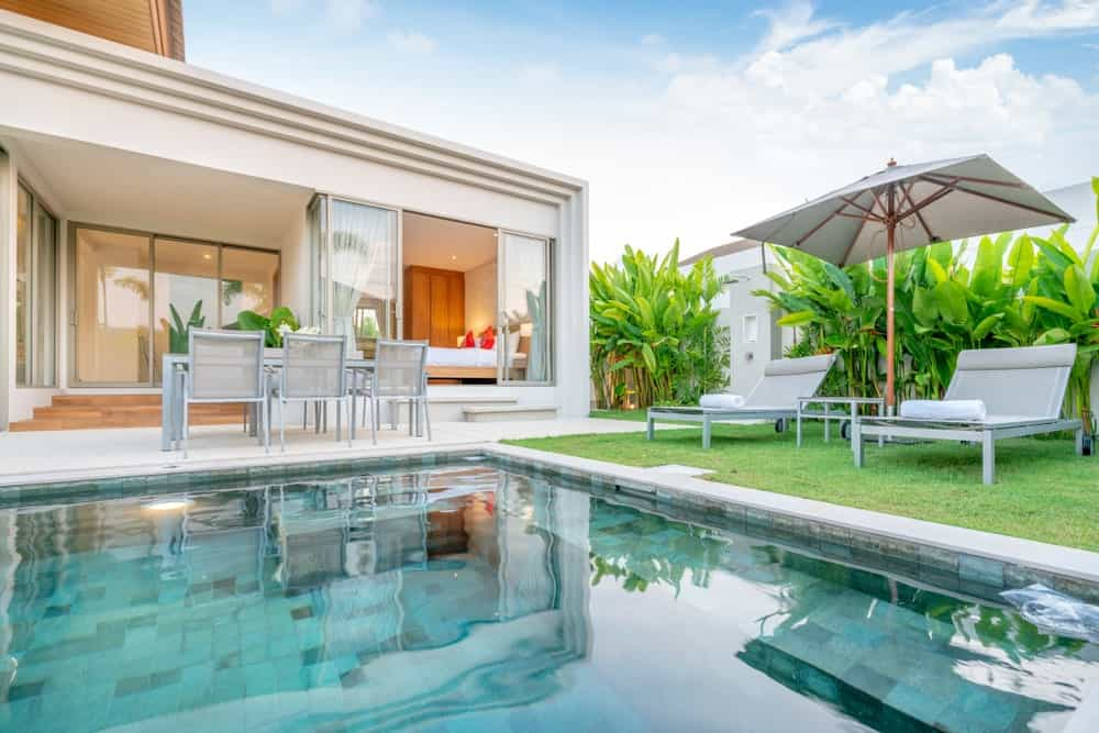 This is a lovely Tropical-style landscape that showcases a swimming pool at the backyard bordered with an outdoor dining area on a concrete flooring on one side and adjacent to that is pair of lawn chairs on a grass lawn with a background of tropical plants.