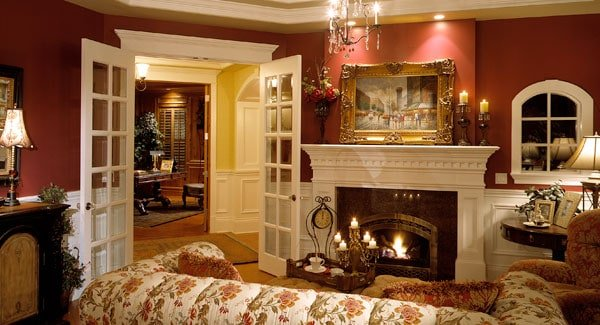 A white french door opens to the living room with floral seats and a warm fireplace fixed against the red walls and white wainscoting across from the floral sofa.