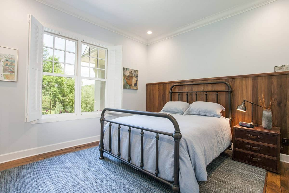 This bedroom has a charming iron pipe bed that pairs quite well with the wood wall panel behind the headboard as well as the large gray area rug that covers most of the hardwood flooring.
