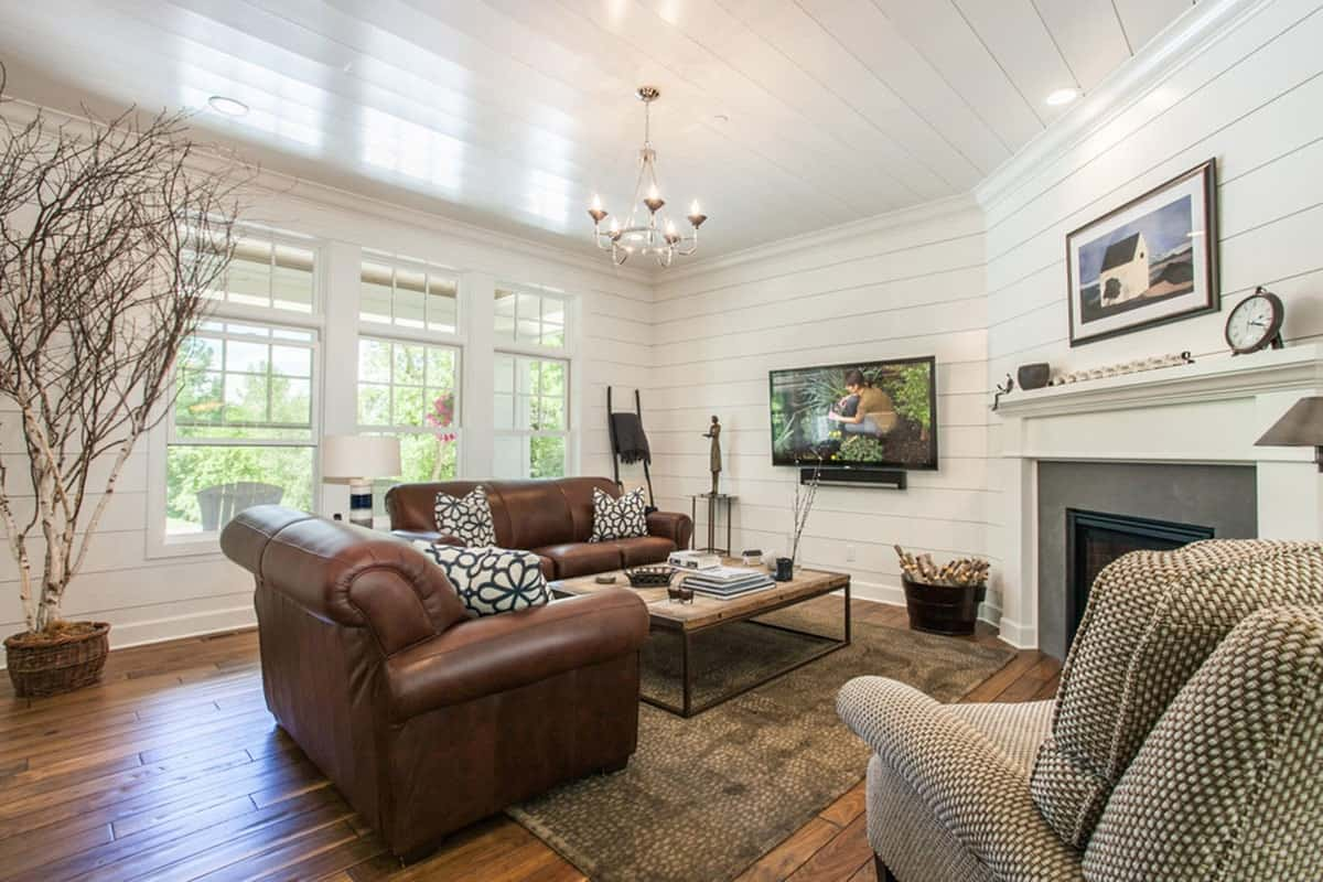 This charming living room has white shiplap walls and ceiling brightened by the tall windows behind the brown leather sofa. This sits across from the corner fireplace that has a white mantle.