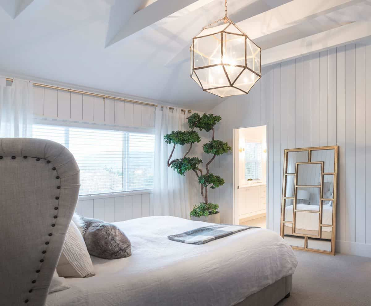 This charming bedroom has a large bed surrounded by white shiplap walls, white arhced ceiling with exposed beams and adornments such as a potted plant and a mirror leaning on the wall.