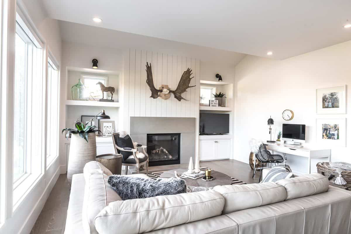 This homey living room has lovely white shiplap walls that augment the warmth of the fireplace that is flanked by built-in cabinets and shelves and topped with decorative antlers. Across from this is the L-shaped beige sofa and its coffee table.