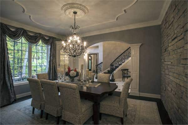 This is the formal dining room of the house with an elegant dark wooden rectangular dining table topped with a majestic decorative chandelier. This chandelier gives warmth to the dark gray walls and the light tone of the area rug underneath.
