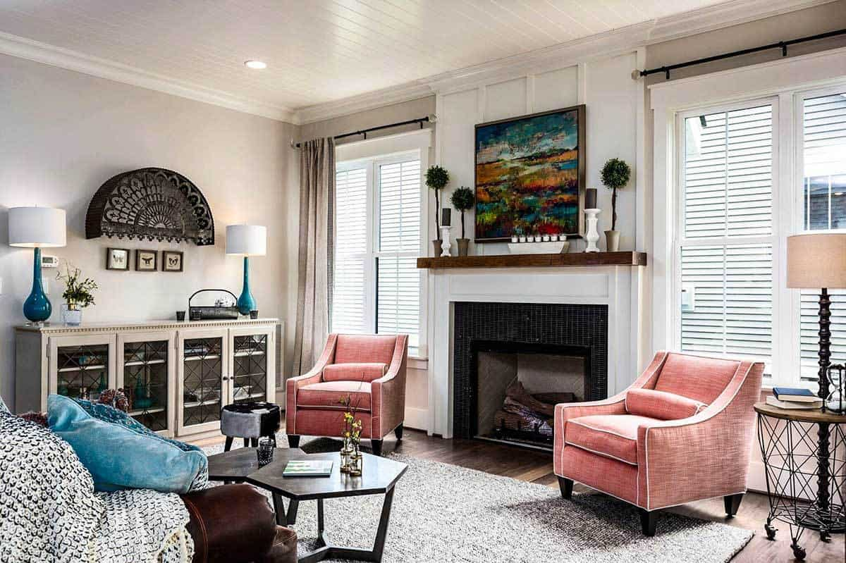 The gorgeous white-mantled fireplace is flanked by a couple of pink cushioned arm chairs placed under windows that bring in natural lighting to brighten the shiplap ceiling and beige walls.