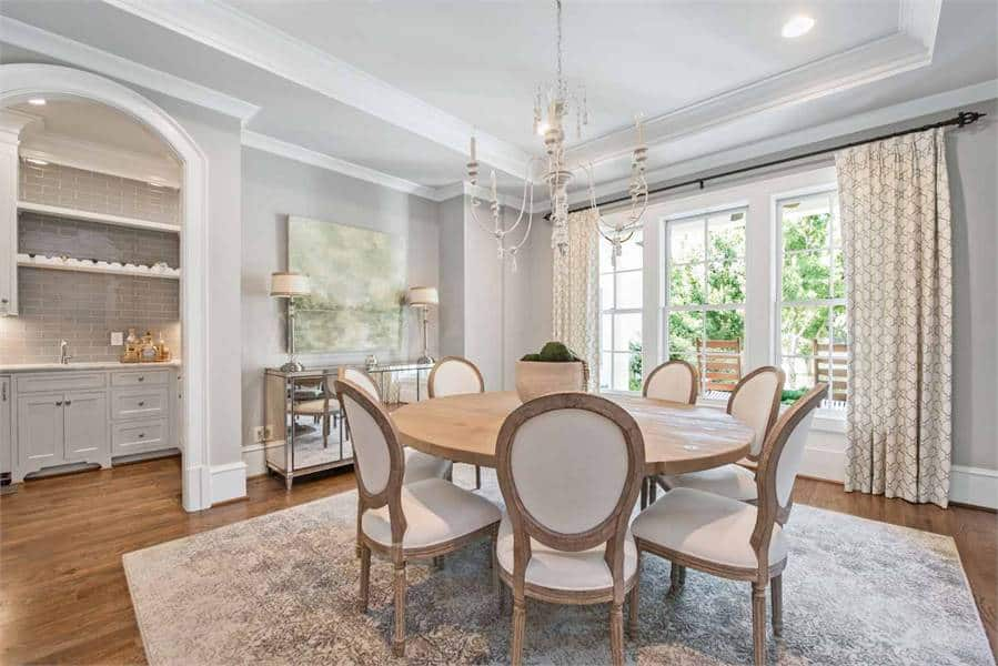 This is a gorgeous formal dining room with beige oval-back chairs surrounding a round wooden dining table that is topped with a thin chandelier.