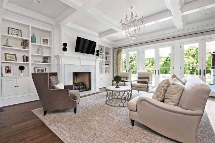This is a bright and airy living room with matching white walls, white coffered ceiling and white mantle for the fireplace across from the cushioned beige sofa and arm chairs. These are all augmented by the brightness of the glass doors.