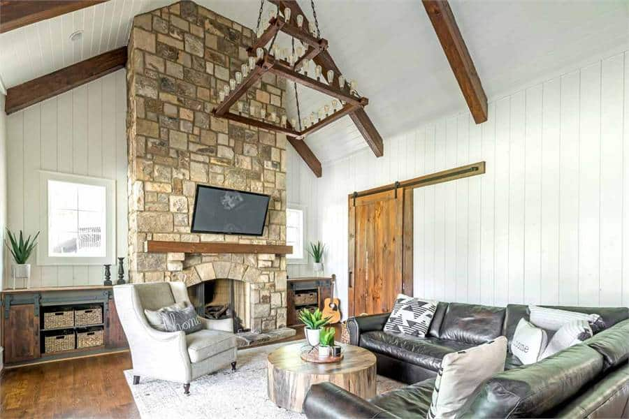 This simple yet gorgeous living room is dominated by the large stone structure that houses the fireplace and the wall-mounted TV above it. This reaches to the cathedral ceiling with exposed beams and hangs a decorative chandelier over the wooden coffee table of the L-shaped sectional leather sofa.