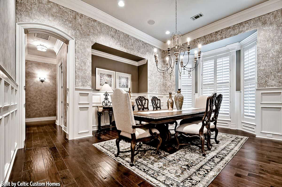 This formal dining room has a dark hardwood flooring that is covered with a patterned area rug. This matches well with the wallpaper above the wainscoting of the walls. These light gray tones makes the dark wooden dining set stand out.