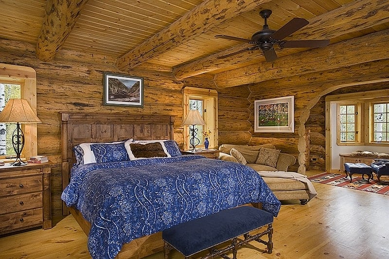This is a spacious bedroom with a bed that has blue sheets and pillows to contrast the wooden headboard and the wooden log beam walls and ceiling adorned with a couple of paintings.