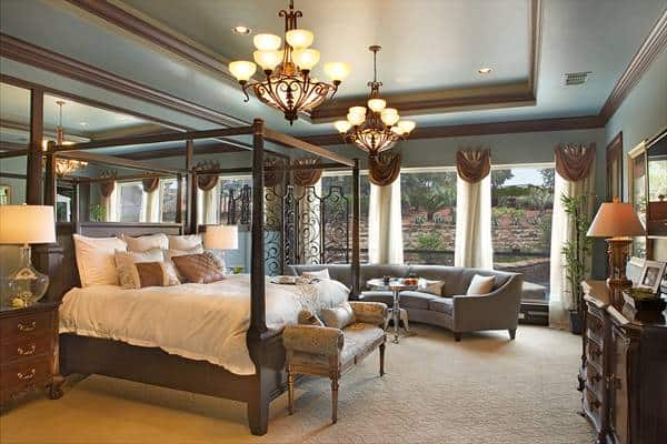 The primary bedroom has a tray ceiling that hangs a couple of chandeliers over the four-poster bed that matches the tone of the dark wooden dresser and bedside drawers.