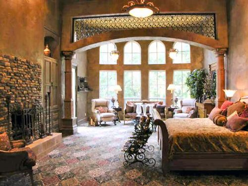 This is the spacious primary bedroom that has a large bed under a tall beige ceiling and has a sitting area on the far side by the tall arched windows.