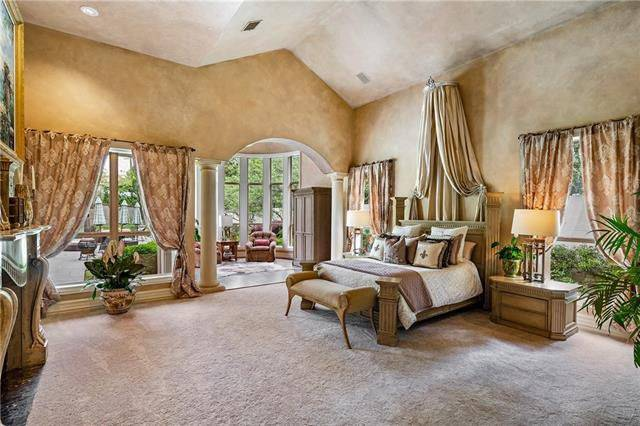 The spacious light gray carpeted flooring of this bedroom is complemented by the beige walls with an archway supported by pillars leading to a lovely sitting area.