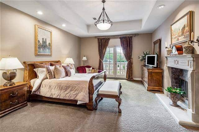 This is a charming bedroom with a wooden sleigh bed across from the large fireplace topped with a lovely painting.