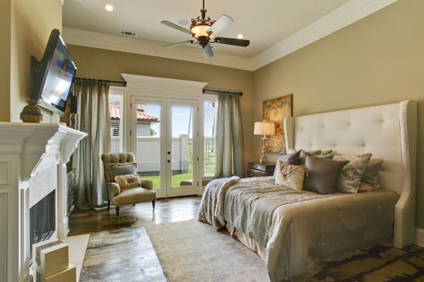 The bed has a large tufted headboard that go quite well with the earthy beige walls of the bedroom. Across from the bed is a large romantic fireplace that is topped with a wall-mounted TV.
