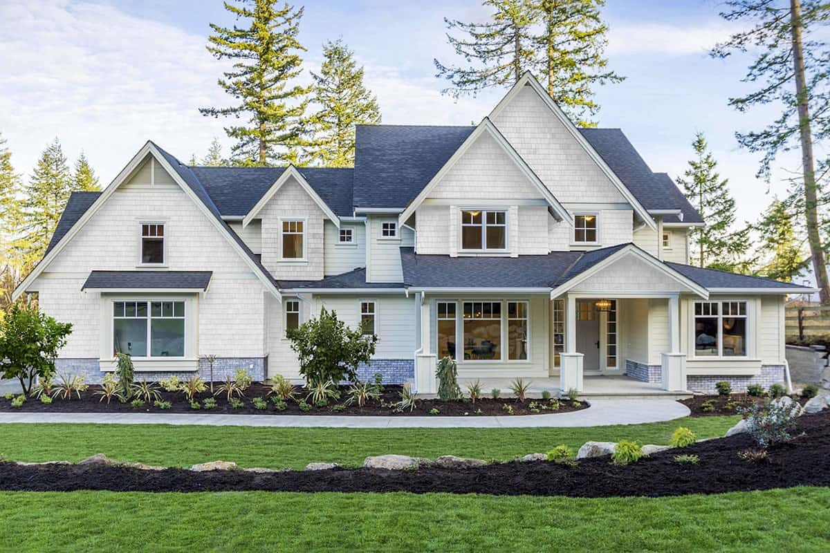 This gorgeous home is foregrounded by a lush couple of green lawns of grass split in two by a row of dark soil waiting for shrubs. The side of the house is also adorned with low shrubs and decorative rocks.