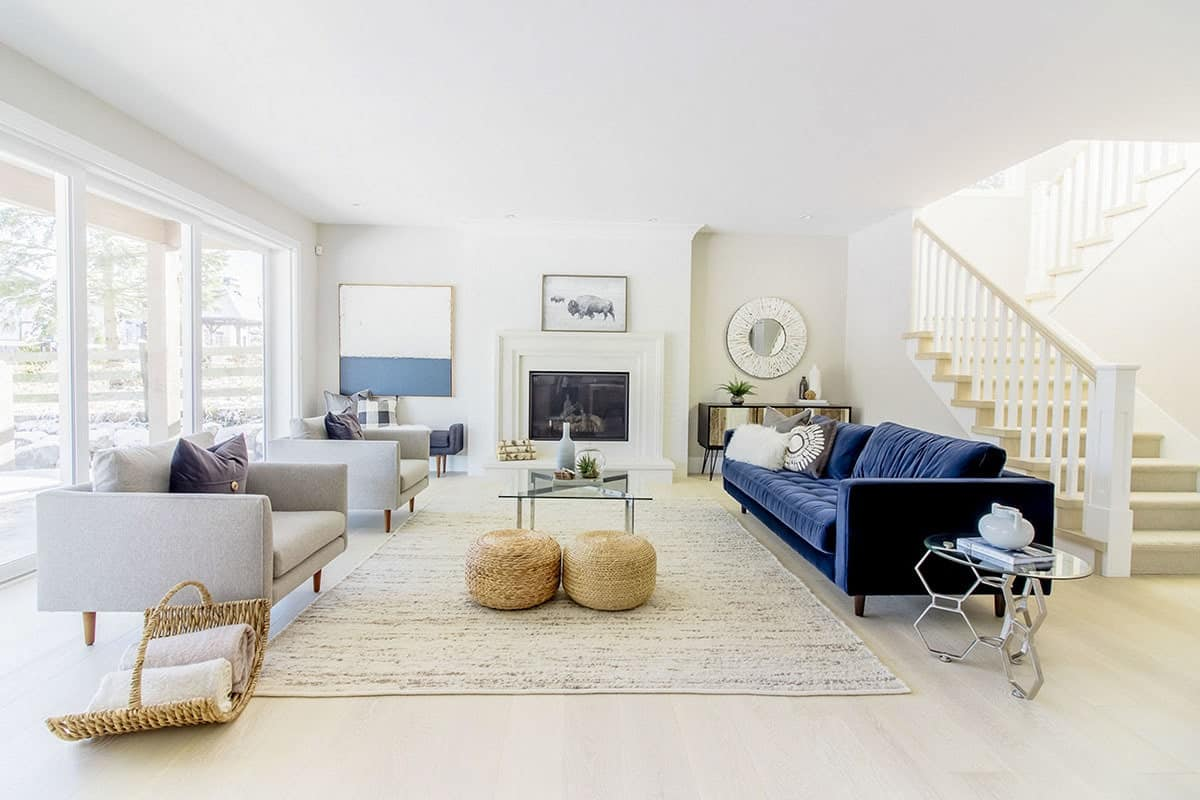 The bright beige ceiling and walls blends well with the light hardwood flooring as well as the mantle of the fireplace. Across from this, the dark blue sofa stands out against the two light gray arm chairs illuminated by large glass windows.
