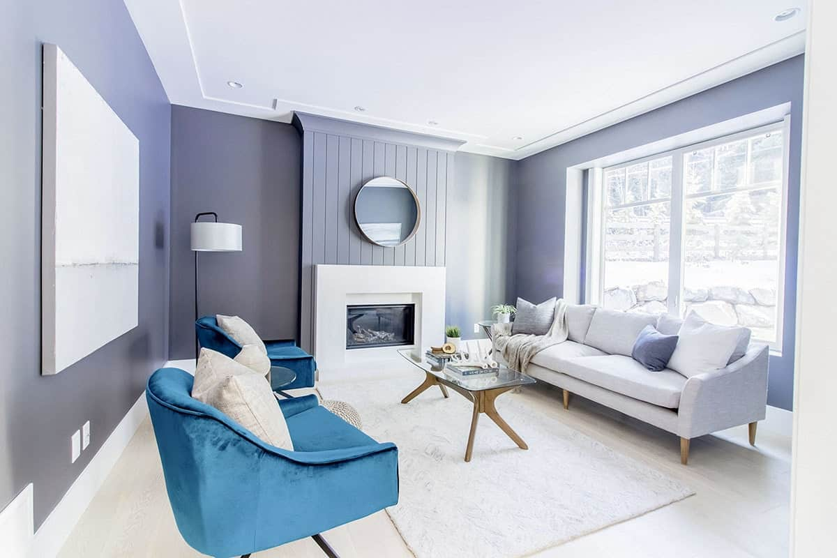 This bright living room has warm gray walls that makes the white mantle of the fireplace stand out along with the light beige sofa under the large glass wall.