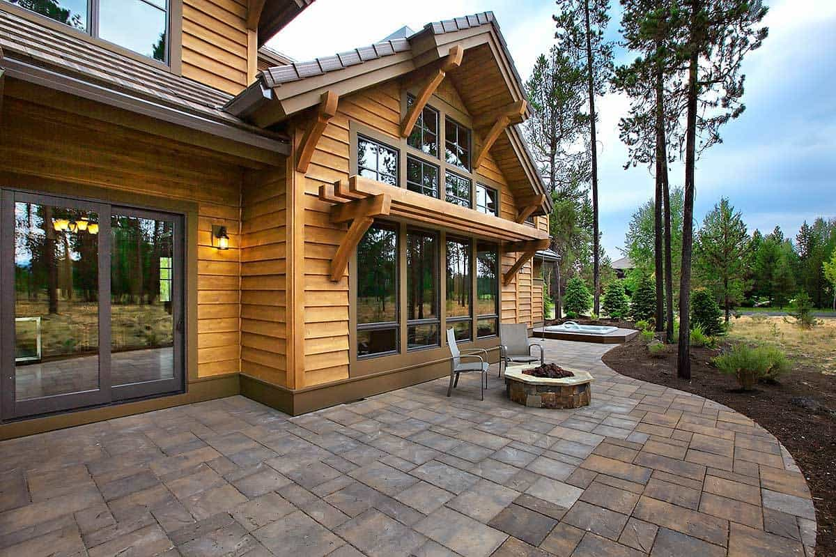 The back of this charming home has lovely stone flooring and walkway that complements the wooden exterior walls of the house and its wide glass windows. This angle view shows that the back of the house has a warm firepit and a jacuzzi-type pool on the far side paired with a background of tall trees.