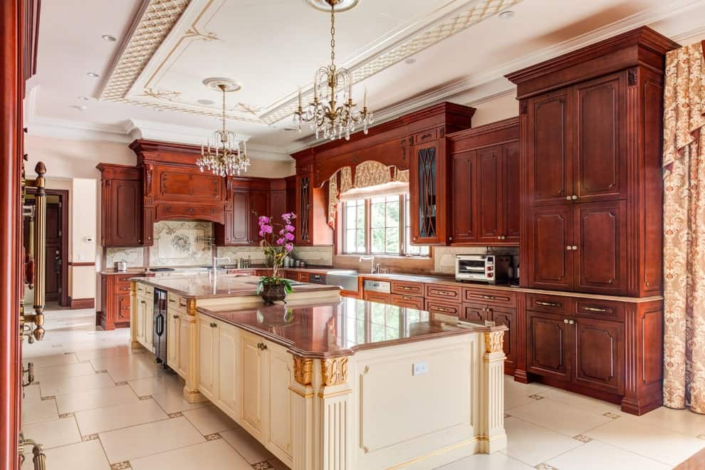 A large kitchen illuminated by fancy chandeliers that hung from the gorgeous tray ceiling. It has wooden cabinetry and a raised breakfast bar topped with granite counters.