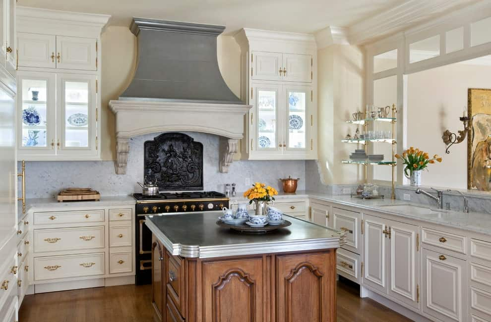 This kitchen boasts a contrasting black range and white cabinetry accented with brass hardware. It includes a wooden central island with a gray countertop complementing with the vent hood.