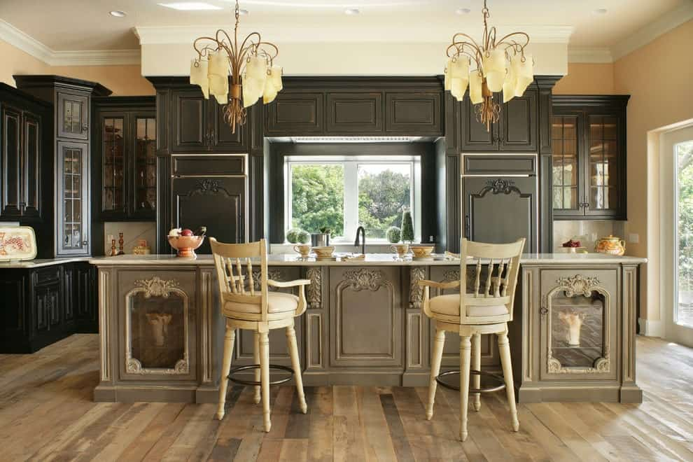 Gorgeous chandeliers hang over the carved island bar paired with beige counter chairs. It is accompanied by black cabinetry and a white framed window that invites natural light in.