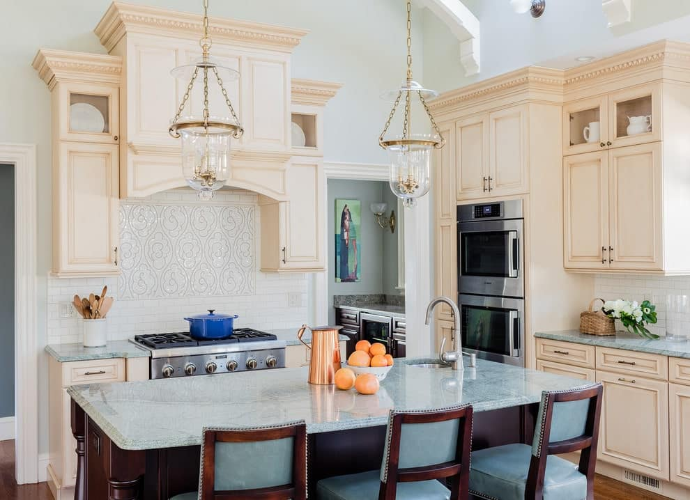 Glass pendant lights illuminate this kitchen showcasing stainless steel appliances and beige cabinetry against the white walls and subway backsplash tiles. It includes a dark wood island bar lined with leather cushioned chairs.