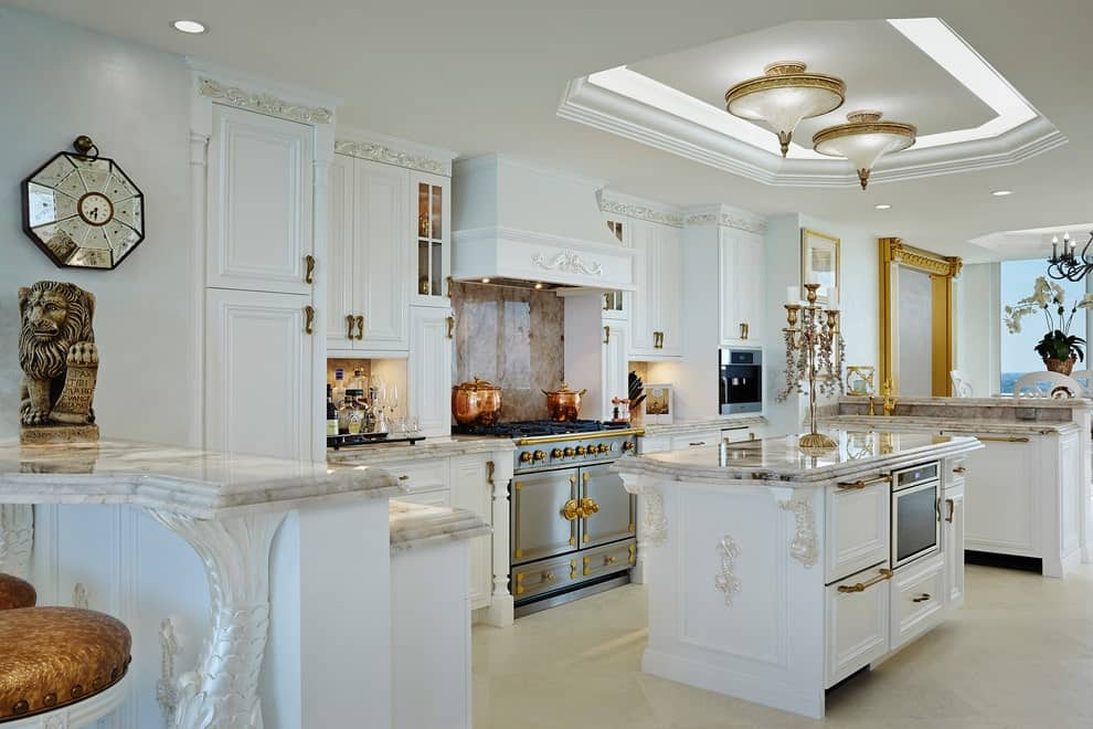 Deluxe kitchen offers white cabinetry and a matching island topped with a marble counter and brass candle holder. It is illuminated by gorgeous semi-flush lights mounted on the tray ceiling.