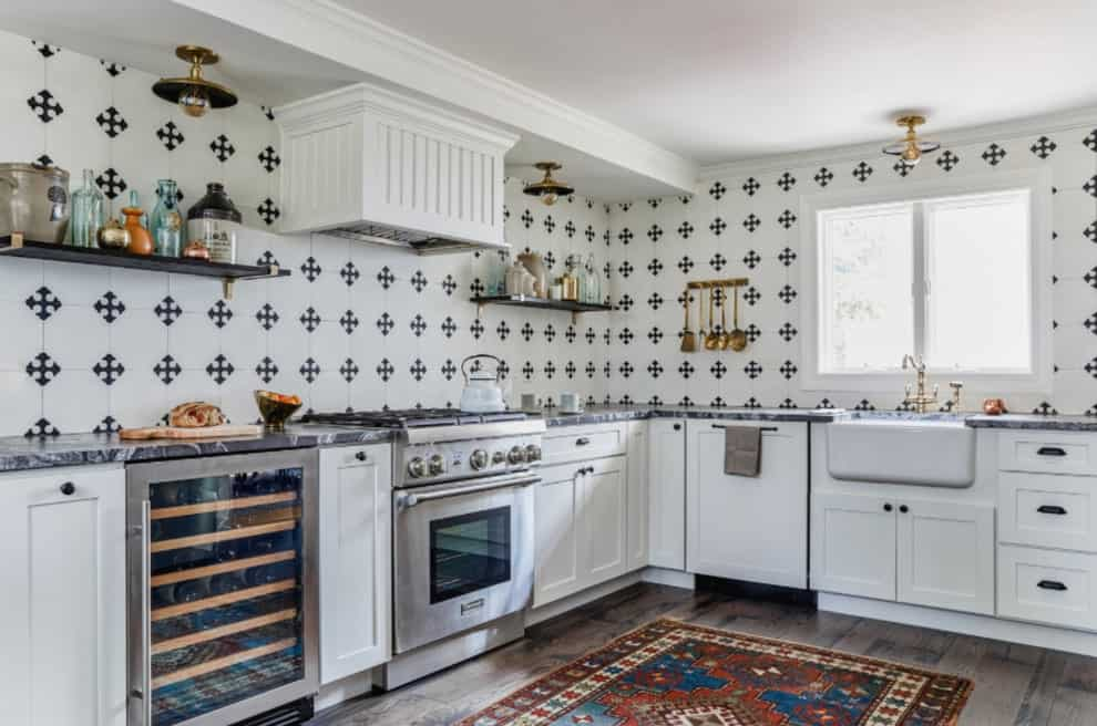 Patterned backsplash tiles add a striking contrast in this bright kitchen with white cabinetry and farmhouse sink fitted with brass fixtures. It has a glazed window and rustic hardwood flooring topped by a printed area rug.