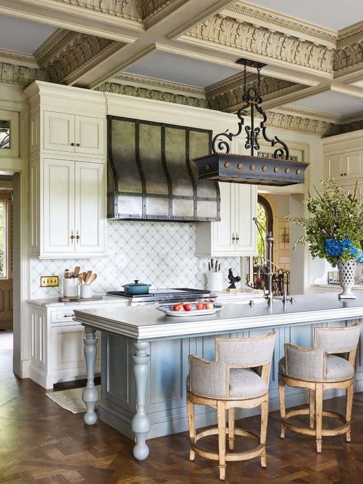 An open kitchen with white cabinetry and rustic vent hood against the white backsplash tiles arranged in a diamond pattern. It includes round counter chairs and a light blue breakfast island with wrought iron pot rack overhead that hung from the coffered ceiling with ornate moldings.