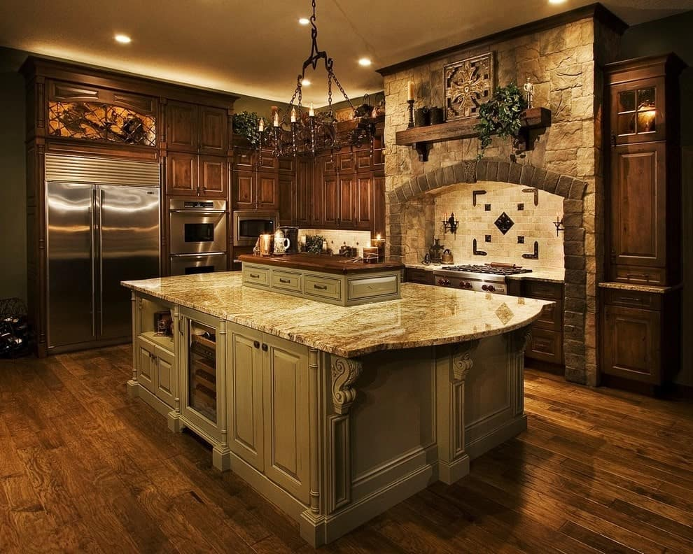 Victorian kitchen with a warm ambiance featuring an immense central island illuminated by candle chandelier and recessed ceiling lights. It is accompanied by natural wood cabinetry and a stone brick alcove hood lined with a rustic mantel.