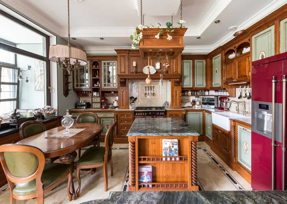 The eat-in kitchen offers multi-colored appliances and wooden cabinetry with sage green doors. It includes an oval dining set and a hanging pot rack fixed above the marble top central island.