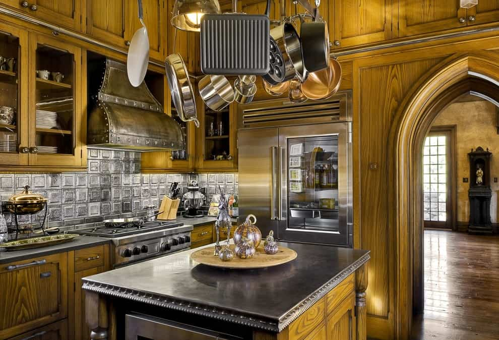 A metal pot rack is suspended over a wooden kitchen island matching with the cabinetry and walls for a harmonious look. This kitchen features stainless steel appliances and a rustic vent hood fixed against the gray backsplash tiles.