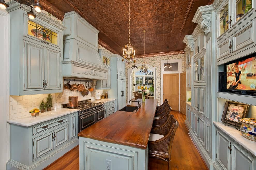 Galley kitchen with gray cabinetry and a long island bar in the middle lined with wicker counter chairs. It is illuminated by candle chandeliers that hung from the ornate ceiling.