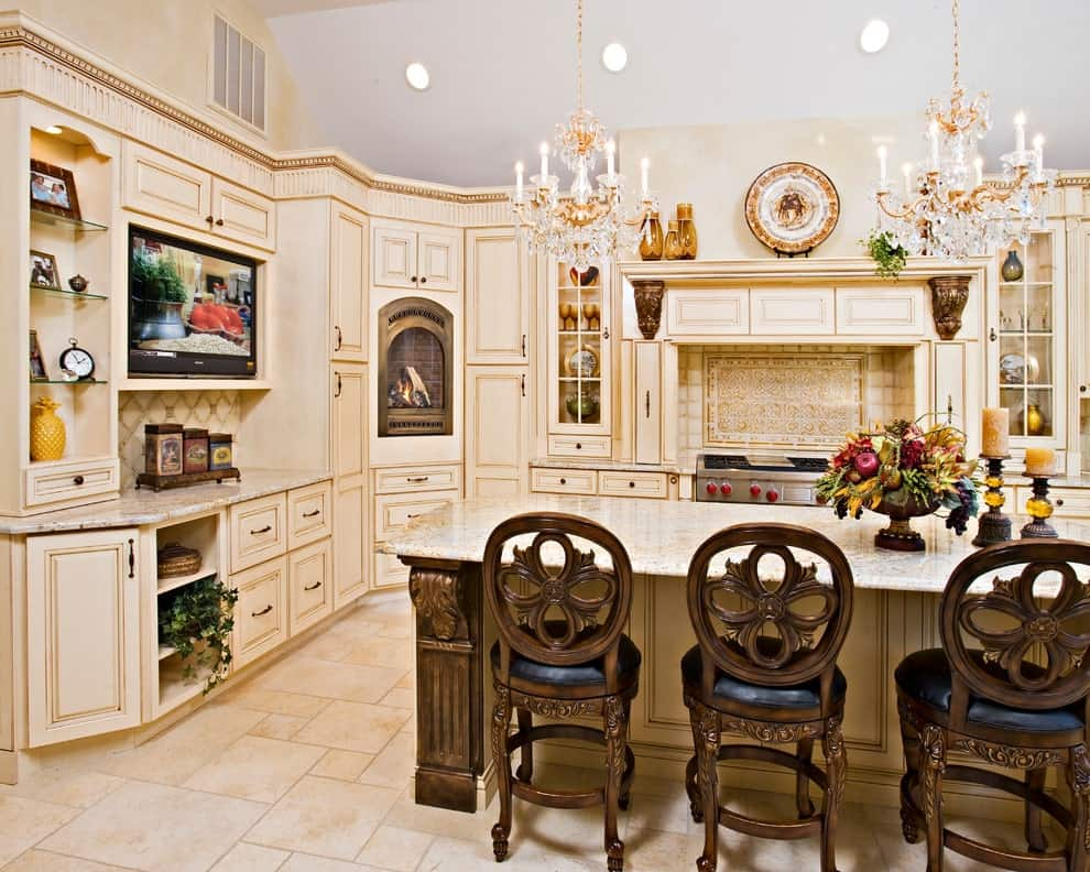 Elegant cushioned chairs sit at a granite top island lighted by fancy chandeliers. It is surrounded by stainless steel appliances and beige cabinetry that blends in with the limestone flooring.