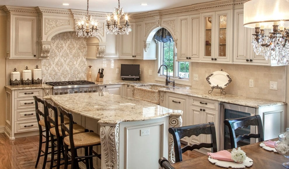 A patterned backsplash sets a classy backdrop to the stainless steel range flanked by beige cabinetry. It is accompanied by candle chandeliers and a granite top island paired with wooden counter chairs.