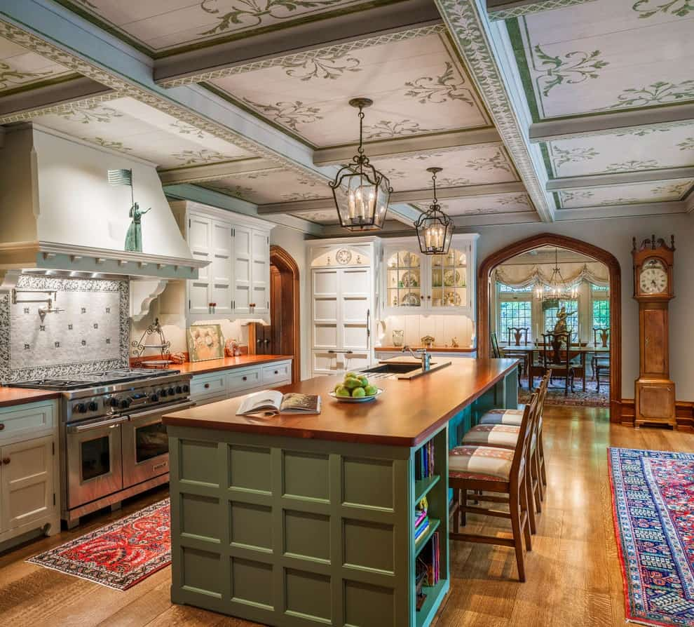 Cozy kitchen with gorgeous coffered ceiling and rich hardwood flooring topped by classic rugs. It has white cabinetry and an immense breakfast bar with cushioned chairs lighted by lantern pendants.