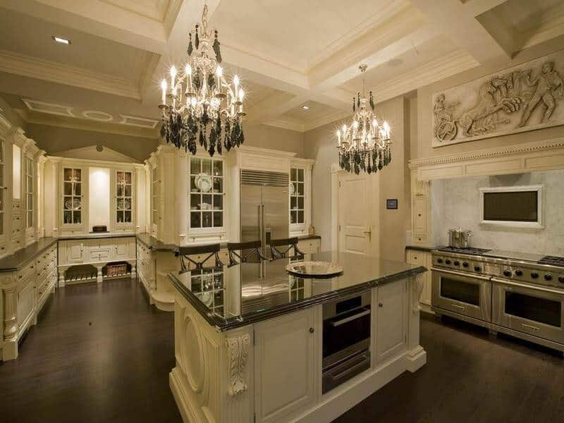 A pair of candle chandeliers that hung from the coffered ceiling illuminates this kitchen offering a black marble top central island and a dual fuel range with alcove hood designed with carved wall art.