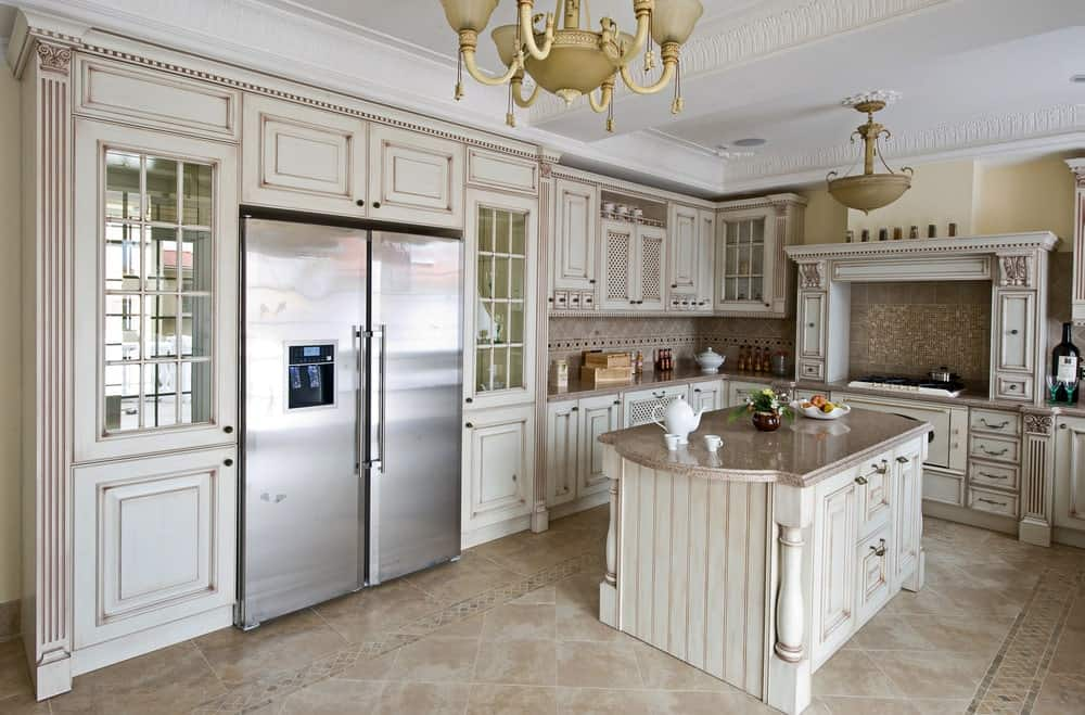 This kitchen showcases a stainless steel fridge flanked by glass front cabinets along with a beadboard island that's topped with a granite counter. It includes vintage pendant lights and a limestone flooring arranged in a diamond pattern.