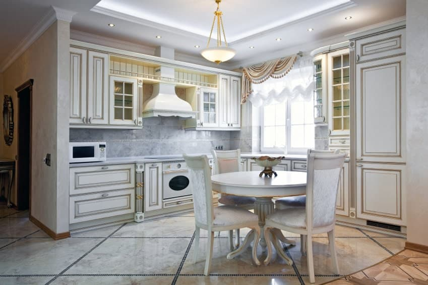 Victorian kitchen with marble flooring and a tray ceiling mounted with recessed lights and a glass dome pendant. It includes white cabinetry and a round dining set topped with a decorative bowl.