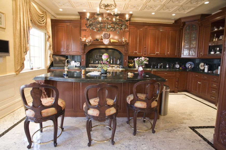 Round cushioned chairs sit at a wooden breakfast bar matching with the cabinetry and alcove hood. This kitchen offers black granite countertops and a candle chandelier that doubles as a pot rack.