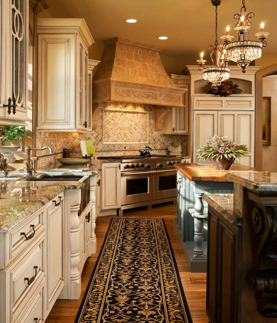 Ambient light from the crystal chandeliers creates a warm and cozy feel in this kitchen with dual islands and white cabinetry flanking a classy black runner that lays on the hardwood flooring.