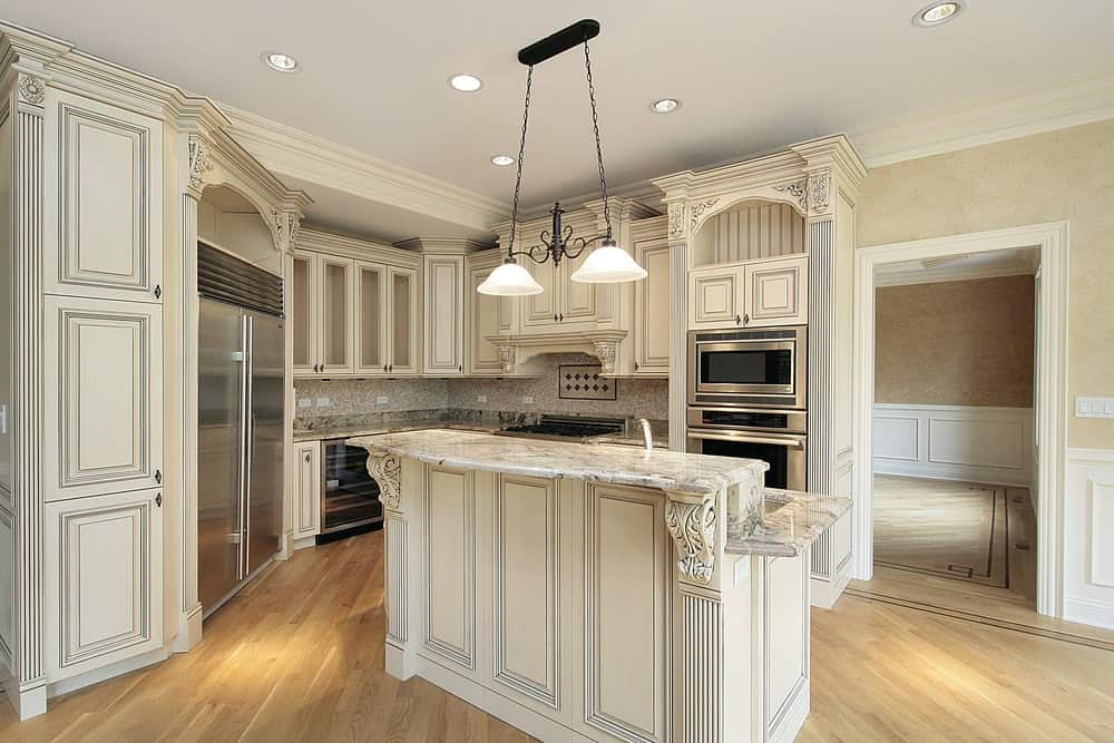 A two-tier kitchen island with marble countertops matches the cabinetry with inset appliances in stainless steel. It is illuminated by vintage pendants and recessed ceiling lights.