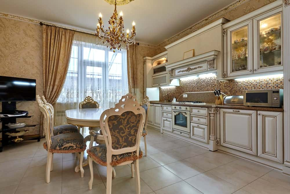 The luxury eat-in kitchen boasts white cabinetry against the stunning mosaic backsplash tiles along with a classy dining set lighted by a fabulous chandelier. It has tiled flooring and glass-paneled windows covered in sheer and floral curtains that blend in with the wallpaper.