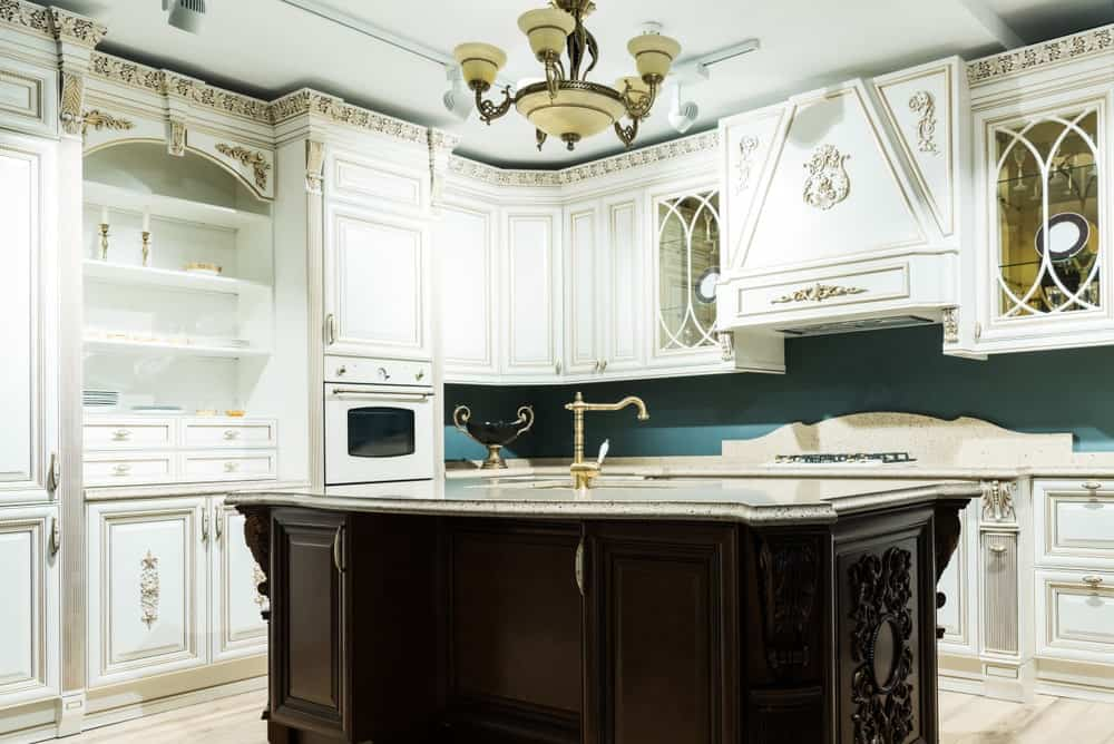 A classic chandelier hangs over the dark wood island fitted with a sink and brass faucet. It is surrounded by white appliances and cabinetry inlaid with ornate carvings.