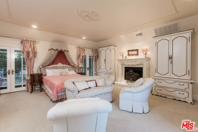 A gorgeous skirted bed with a canopy overhead brings a pop of color in this primary bedroom with beige carpet flooring and a pair of French doors dressed in silk draperies. It is accompanied by cozy seats and white wardrobes flanking the fireplace.