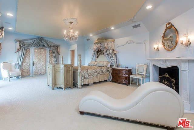 The spacious primary bedroom showcases a white wingback chair next to the glazed windows along with a skirted bed that's illuminated by a classy chandelier. There's a sleek chaise lounge by the fireplace accented with a gorgeous round mirror and wall sconces.