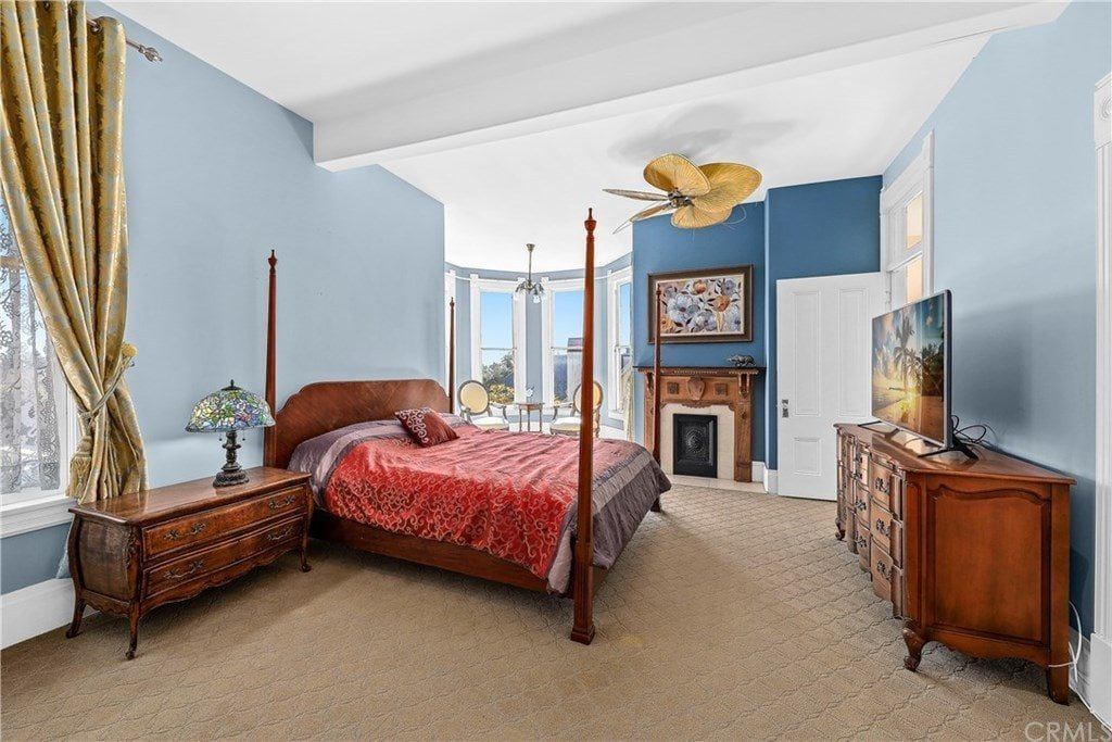 Blue primary bedroom with a corner fireplace and a four-poster bed facing the dresser that's topped with a flat-screen TV. It is completed with a seating area by the bay window lighted by a sleek chandelier.