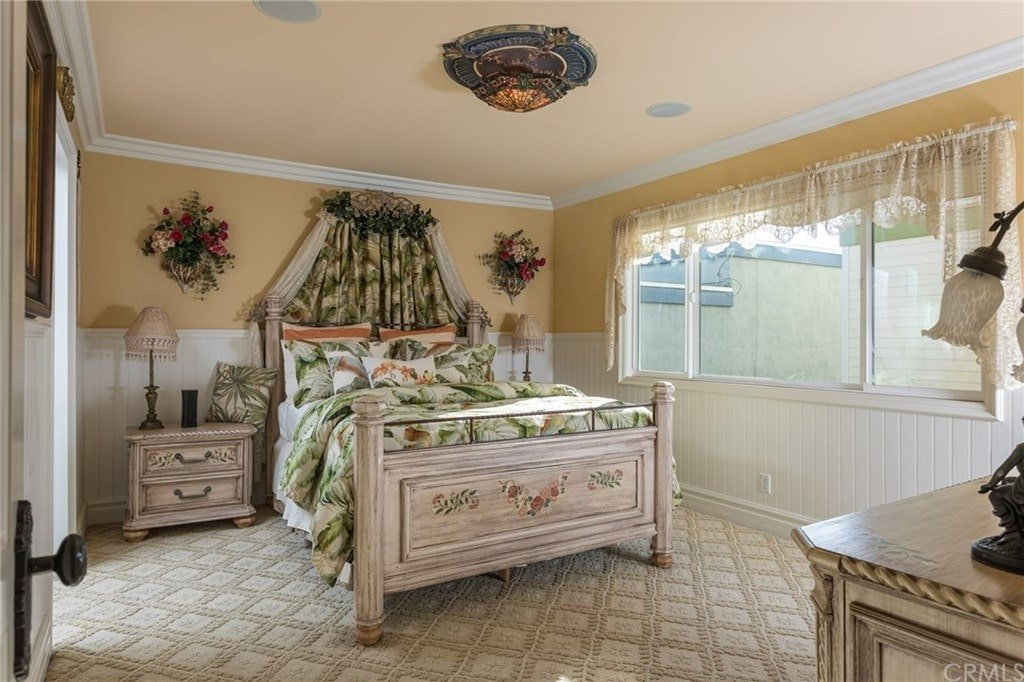 A gorgeous flush mount light illuminates this primary bedroom along with natural light flowing in through the glass paneled windows. It boasts a lovely wooden bed flanked by matching nightstands and decorative wall flowers.