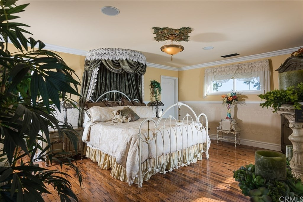 A tall potted plant creates a tropical feel in this primary bedroom with polished hardwood flooring and glazed windows dressed in sheer valances. It features a white metal bed with a classy canopy overhead illuminated by a warm pendant light.